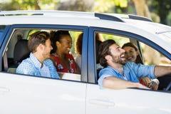 Groupe d'amis ayant l'amusement dans la voiture Photo stock