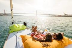 Groupe d'amis ayant l'amusement dans le bateau en rivière Photos stock