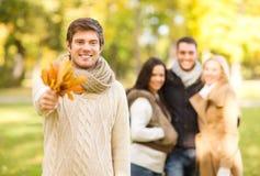 Groupe d'amis ayant l'amusement dans le parc d'automne Photographie stock libre de droits