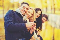Groupe d'amis ayant l'amusement dans le parc d'automne Photo stock