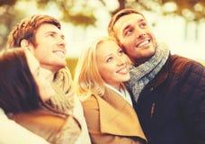 Groupe d'amis ayant l'amusement dans le parc d'automne Photos stock