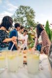 Groupe d'amis ayant l'amusement dans un barbecue d'été Image stock