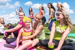 Groupe d'amis ayant l'amusement dans un parc le jour ensoleillé Photographie stock