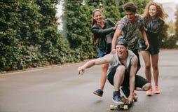 Groupe d'amis ayant l'amusement dehors avec la planche à roulettes Images stock