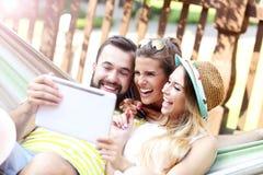 Groupe d'amis ayant l'amusement dehors en été Image stock