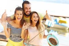 Groupe d'amis ayant l'amusement dehors en été Photographie stock libre de droits