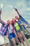 Groupe d'amis ayant l'amusement dehors sur un coucher du soleil d'été Photographie stock