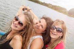 Groupe d'amis ayant l'amusement dehors sur un lac Photographie stock libre de droits
