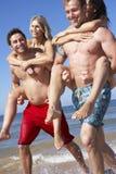 Groupe d'amis ayant l'amusement des vacances de plage ensemble Images stock