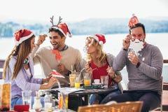 Groupe d'amis ayant l'amusement en café tenant la moustache et le bâton de lèvres artificiels images libres de droits