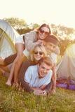 Groupe d'amis ayant l'amusement en dehors des tentes des vacances de camping Photographie stock