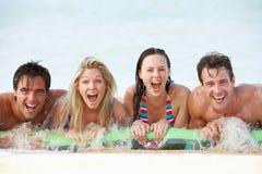 Groupe d'amis ayant l'amusement en mer sur le matelas pneumatique Photographie stock libre de droits
