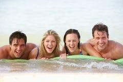 Groupe d'amis ayant l'amusement en mer sur le matelas pneumatique Images libres de droits