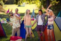 Groupe d'amis ayant l'amusement ensemble au terrain de camping Image stock