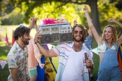 Groupe d'amis ayant l'amusement ensemble au terrain de camping Photographie stock libre de droits