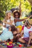 Groupe d'amis ayant l'amusement ensemble dans le parc Photo stock
