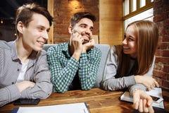 Groupe d'amis ayant l'amusement ensemble dans un café Photographie stock