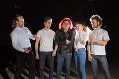 Groupe d'amis ayant l'amusement ensemble extérieur dans une nuit et une lumière derrière Photos libres de droits