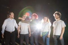 Groupe d'amis ayant l'amusement ensemble extérieur dans une nuit et une lumière derrière Photo libre de droits