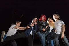 Groupe d'amis ayant l'amusement ensemble extérieur dans une nuit et une lumière derrière Images stock