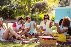 Groupe d'amis ayant l'amusement ensemble près de campervan Photographie stock