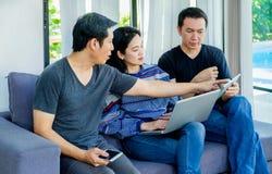 Groupe d'amis ayant l'amusement et employant le mobile numérique de dispositif, recouvrement Images libres de droits