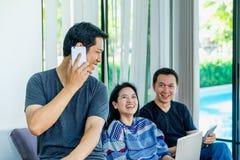 Groupe d'amis ayant l'amusement et employant le mobile numérique de dispositif, recouvrement Photo stock