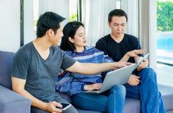 Groupe d'amis ayant l'amusement et employant le mobile numérique de dispositif, recouvrement Image stock