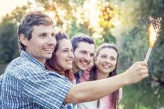 Groupe d'amis ayant l'amusement extérieur sur un coucher du soleil d'été Image libre de droits