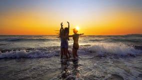 Groupe d'amis ayant l'amusement fonctionnant en bas de la plage au coucher du soleil Photos libres de droits