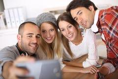 Groupe d'amis ayant l'amusement prenant le selfie Photos stock