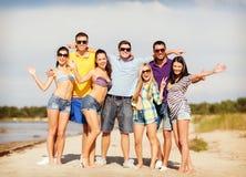 Groupe d'amis ayant l'amusement sur la plage Photographie stock