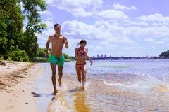 Groupe d'amis ayant l'amusement sur la plage Photos stock