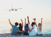 Groupe d'amis ayant l'amusement sur la plage avec des avions de vol Image stock