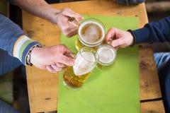 Groupe d'amis ayant la bière dans une barre Images stock