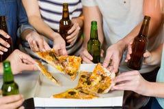 Groupe d'amis ayant la bouteille de bière et de pizza dans la partie Image stock