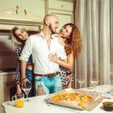 Groupe d'amis ayant la partie d'amusement à la maison avec de l'alcool et la pizza Photographie stock