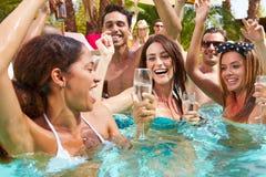 Groupe d'amis ayant la partie dans la piscine buvant Champagne Photo stock