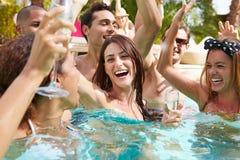 Groupe d'amis ayant la partie dans la piscine buvant Champagne Image libre de droits