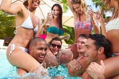 Groupe d'amis ayant la partie dans la piscine buvant Champagne Image stock