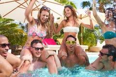 Groupe d'amis ayant la partie dans la piscine buvant Champagne Photo libre de droits