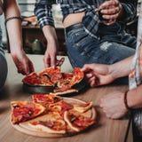 Groupe d'amis ayant la partie et mangeant de la pizza Photo libre de droits