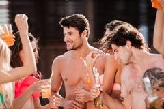 Groupe d'amis ayant la partie par la piscine Photographie stock