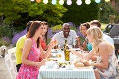 Groupe d'amis ayant le barbecue extérieur à la maison Photographie stock