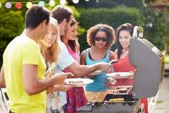 Groupe d'amis ayant le barbecue extérieur à la maison Image libre de droits