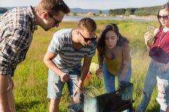 Groupe d'amis ayant le BBQ au lac en été Image stock
