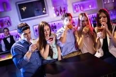 Groupe d'amis ayant le cocktail au compteur de barre Photos stock
