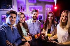 Groupe d'amis ayant le cocktail au compteur de barre Photographie stock