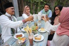 Groupe d'amis ayant le pain grillé de thé à la table dinant pendant le Ramadan Photos libres de droits