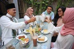 Groupe d'amis ayant le pain grillé de thé à la table dinant pendant le Ramadan Images libres de droits